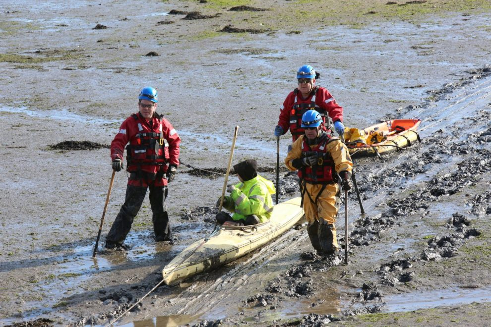 rescue operation to pull man from a canoe stuck in the mud