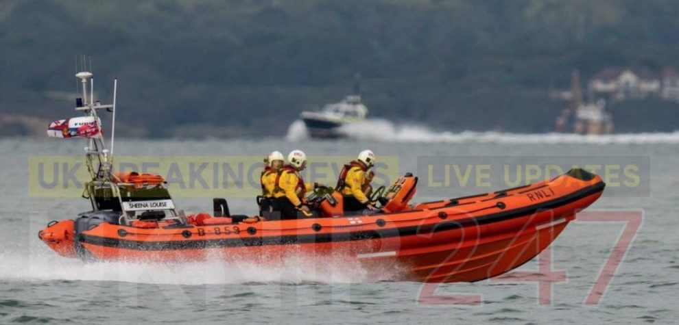 two dog owners walking their five small dogs rescued by cowes lifeboat